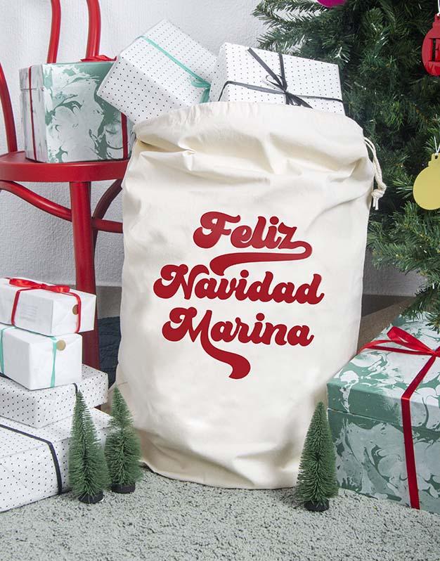 Saco Navidad 70,S personalizado con el nombre. Este diseño retro inspirado en las tipografías hippies de los años 70 está pensado para todos los amantes de la Navidad. Podrás usarlo tanto para regalos de Papá Noel como Reyes Magospero solo si has sido muy buen@.